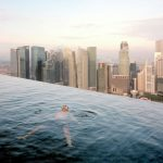 """Ein Gast geniesst den Swimming Pool im 57. Stockwerk des Marina Bay Sands Hotel, mit der Silhouette des """"Central"""", des Finanzviertels von Singapur, hinter ihm. © Paolo Woods und Gabriele Galimberti, Singapur, 2015"""